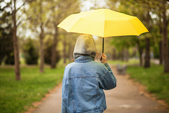 person walking in park under yellow umbrella